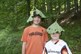Zwei Jungs in bunten T-Shirts waren ebenfalls dabei und bastelten sich aus großen Pestwurzblättern Sonnenhüte.