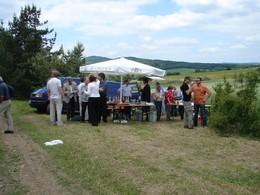 Die Gäste scharen sich an einem Imbissstand. Unter einem großen Sonnenschirm geschützt werden Bratwürste und belegte Brote angeboten.