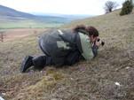 Ein junger Mann hockt mit einem Fotoapparat auf einem noch wintergrauen Kalkmagerrasen und fotogafiert Küschenschellen.