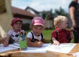 Drei Kinder sitzen bei der 1175-Jahrfeier in Fischbach an der Kinderbiergarnitur und malen das Logo des Hexenpfades aus.