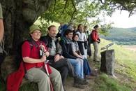An derselben Stelle verweilt eine Gruppe Wanderer während der geführten Exkursion auf der Bank und genießt die Aussicht.