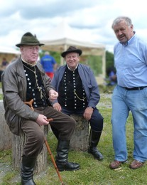 Zwei Schäfermeister in traditioneller Tracht und ein Vertreter des Schafzuchtverbandes sitzen bei Bratwurst und Sonnenschein beieinander.