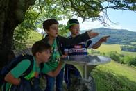 Drei kleine Jungs (4. Klasse) stehen unter einer Hutebuche am Hexenpfad und fachsimpeln gestenreich über die Lage der Dörfer und Anhöhen, die auf der Panoramatafel vermerkt sind.