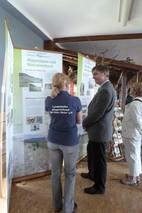Die Projektleiterin Frau Ludwig steht mit dem Amtsleiter des Umweltamtes vom Wartburgkreis, Herrn Dr. Feder, vor einem der Banner der Wanderausstellung und erklärt ihm die Idee hinter der Ausstellung