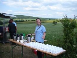 Eine junge Mitarbeiterin der Agrargenossenschaft Helmershausen schenkt an einem langen Tisch Kaffee aus.