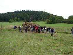 Schüler einer 9. Klasse des Rhöngymnasiums beräumen mit Rechen das Mahdgut von einer naturschutzfachlich wertvollen Feuchtfläche am Grimmelbachspeicher und laden es auf einen Anhänger.