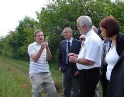 """Herr Meyer vom Projektteam """"100 Äcker"""" steht mitten im Acker, hält ein Pflänzchen in die Höhe und erklärt Frau Dr. E. Nickel (BMU), Herrn Reinholz und Herrn Rommel (ALF) die Besonderheiten der Segetalflora."""