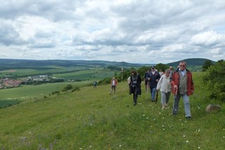 Eine Wandergruppe auf blühenden Magerrasen am Südhang der Hohen Geba. Im Ihntergrund sieht man Helmershausen, den Wallenberg und die Altmark.