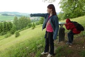 Ein Mädchen steht an der Panoramastation des Hexenpfades und deutet auf etwas in weiter Ferne.