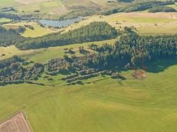 Das Schrägluftbild zeigt den Nordhang der Hardt, wobei das Kalkflachmoor mit einem Pfeil markiert ist. Zum Zeitpunkt der Aufnahme wurde in diesem Jahr in der Folgepflege übergeben. Eine späte einschürige Mahd wurde durch die Untere Naturschutzbehörde